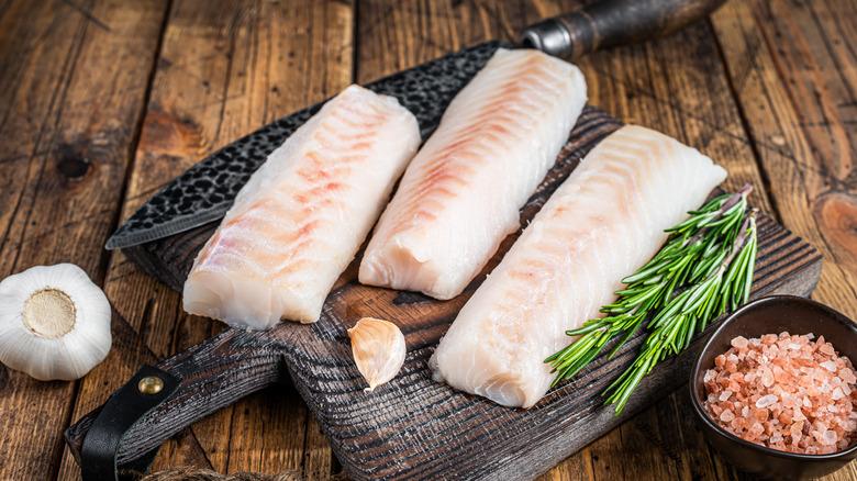 Pink cod filets on a brown wood board