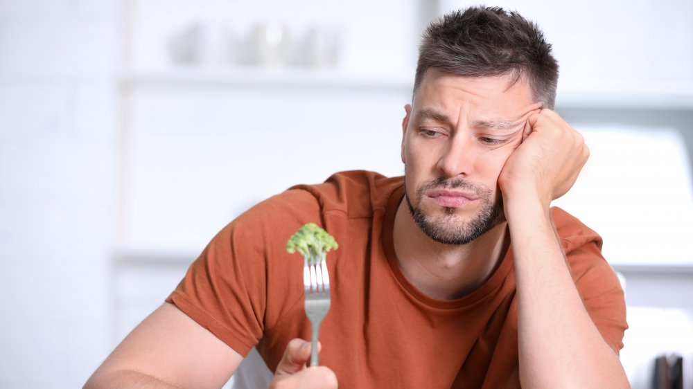 Disappointed man eating broccoli