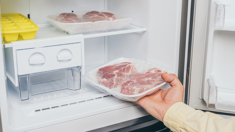 Person taking frozen meat out of freezer