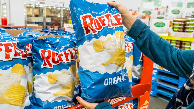 A person holding a bag of blue Ruffles