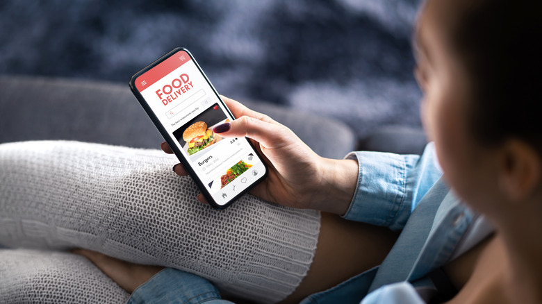 Woman using food delivery app on phone