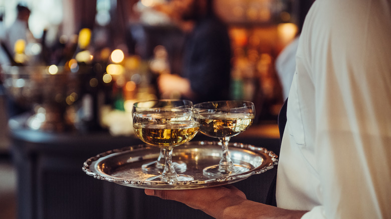 Waiter carrying tray of drinks