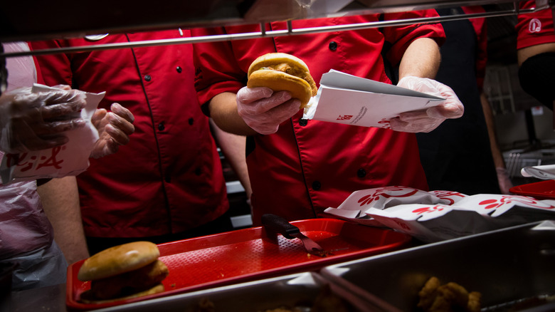 Chick-fil-A workers stuffing burgers