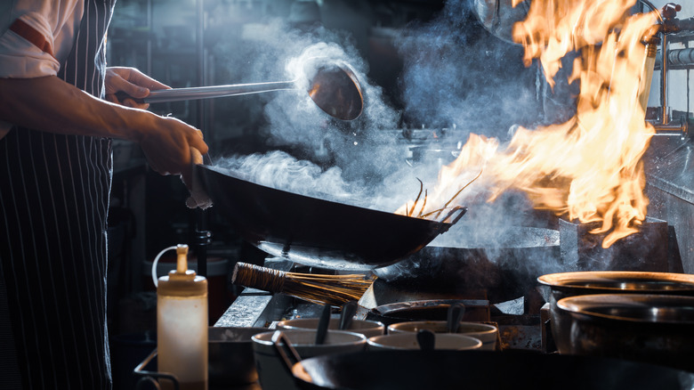 Chef stirring pan over flame
