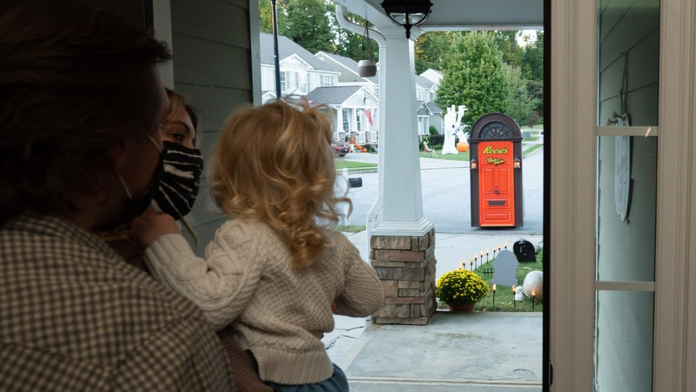 family wearing mask watching the Reese's Trick-or-Treat Door approach