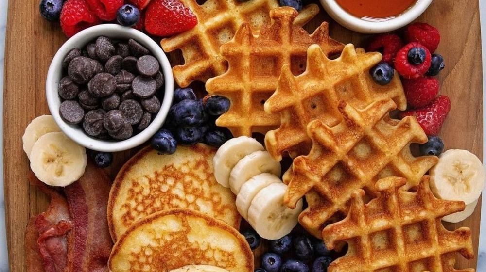 Breakfast charcuterie board with pancakes, waffles, and more