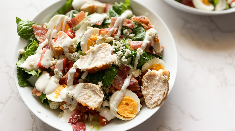 cobb salad with chicken and boiled eggs in white bowls