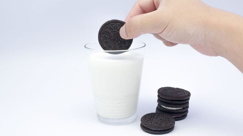 Hand dunking Oreo into glass of milk