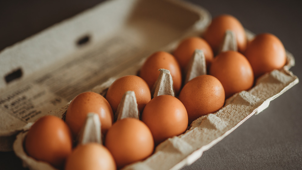 A carton of eggs on a black background
