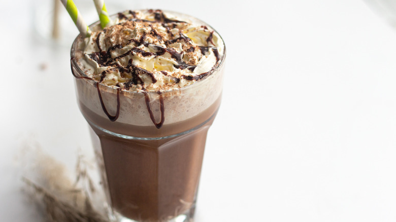 chocolate frappuccino in glass with straws and chocolate drizzle