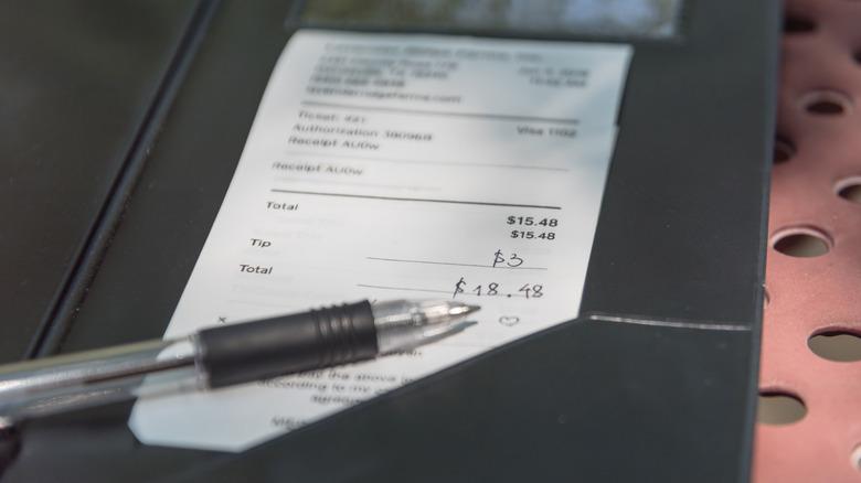 White restaurant bill and pen