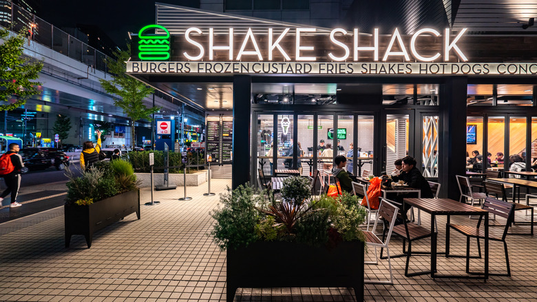 Outside a Shake Shack location with illuminated logo