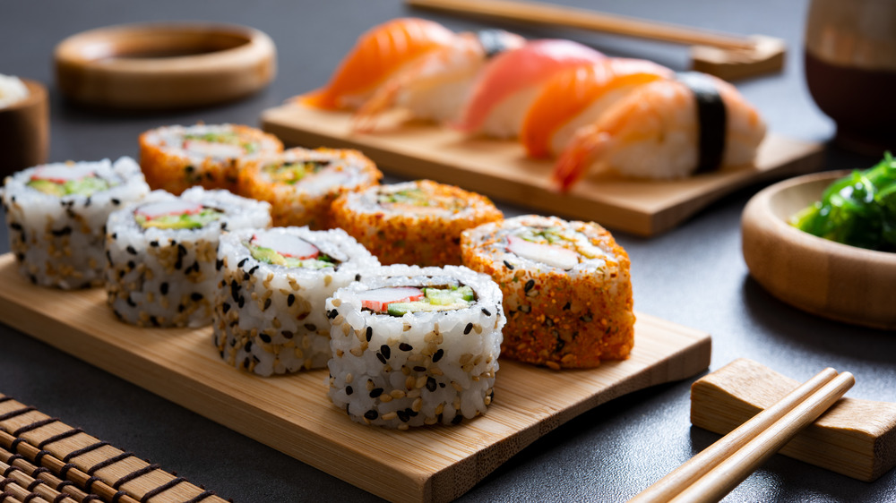 Various sushi rolls set on wooden plates