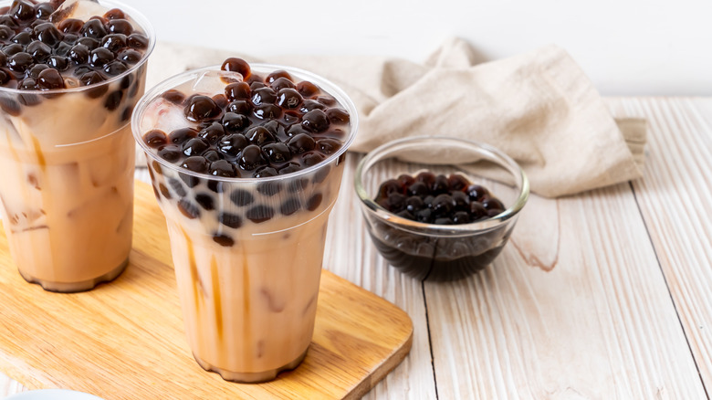 Two boba teas and bowl of tapioca pearls