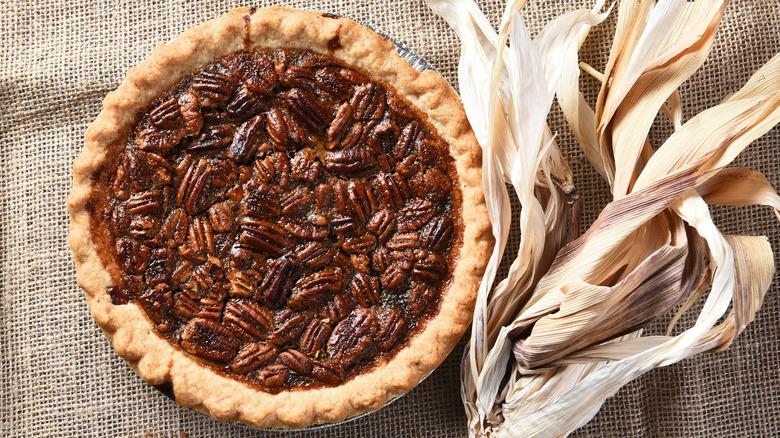 Pecan pie with corn husk on burlap background