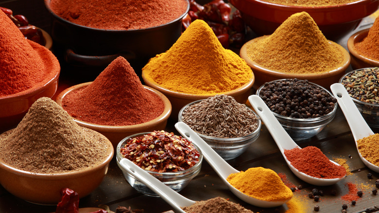 Colorful spices in bowls and on spoons