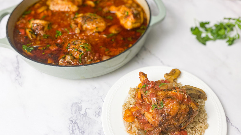 chicken cacciatore in a pan and plated in white dish on bottom right