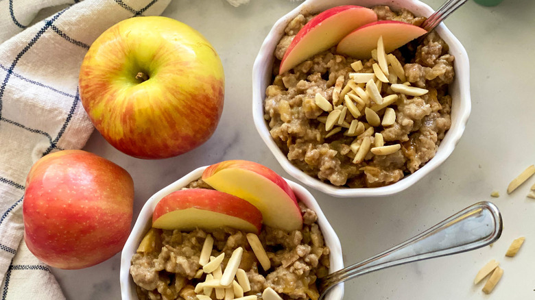 bowls of apple cinnamon oatmeal with whole and sliced apples