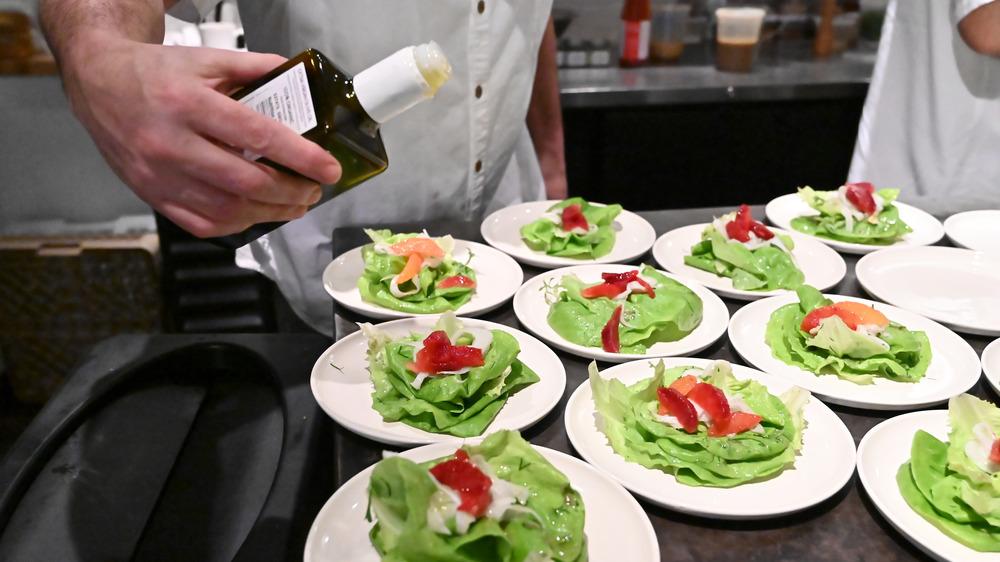 restaurant worker preparing a line of salads