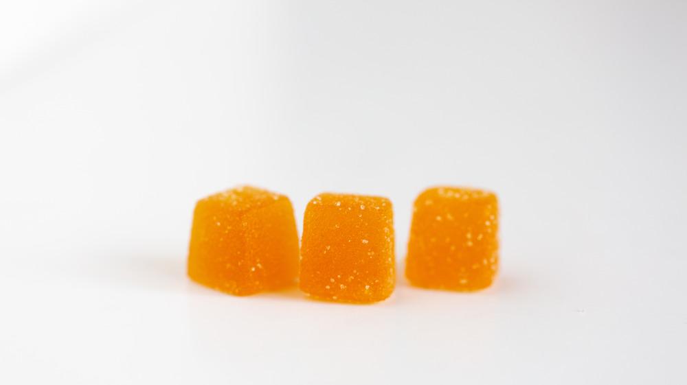 Orange gummy vitamins on background