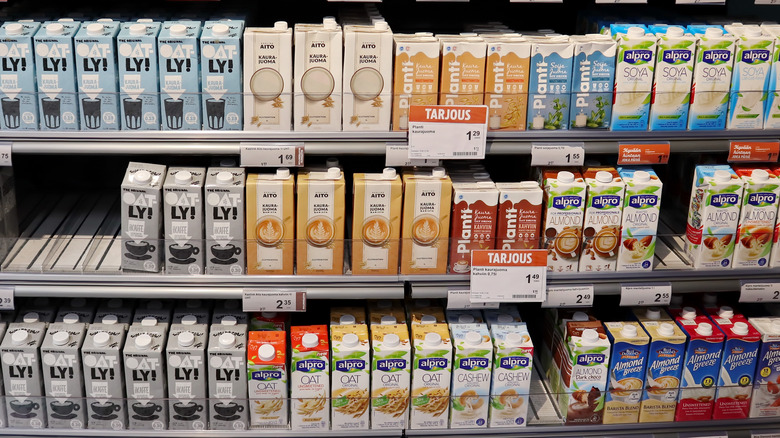 Non-dairy milk cartons on shelves in supermarket