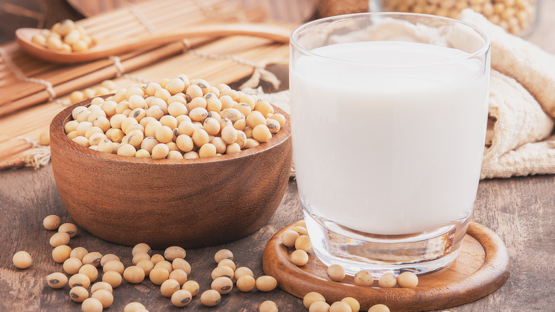 Soy milk in glass next to soybeans