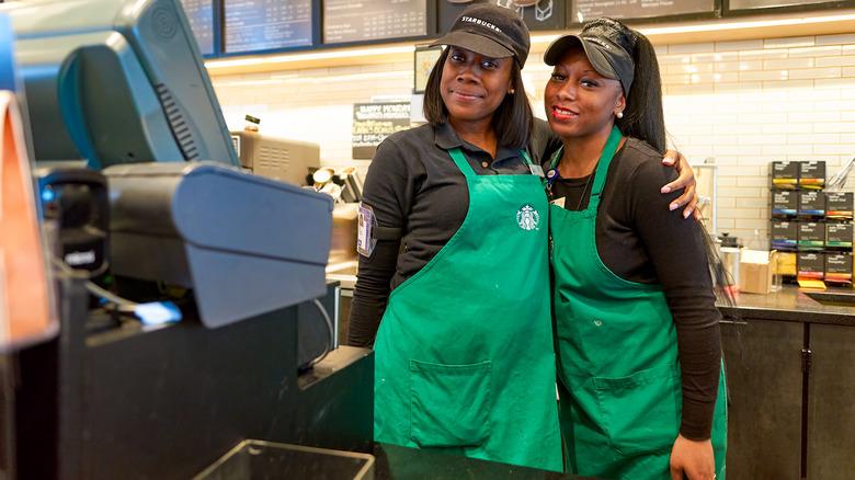 Two Starbucks baristas embracing