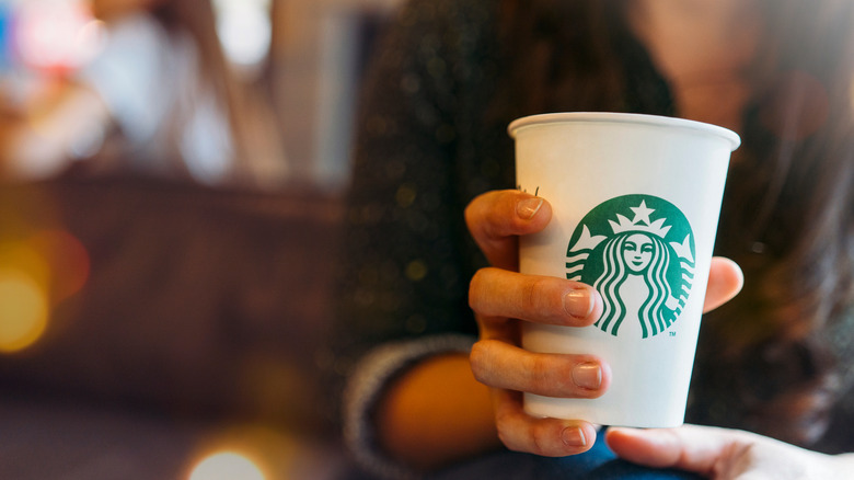 woman with cup of Starbucks coffee