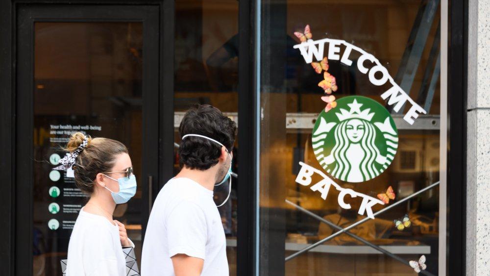 Masked couple walking by Starbucks