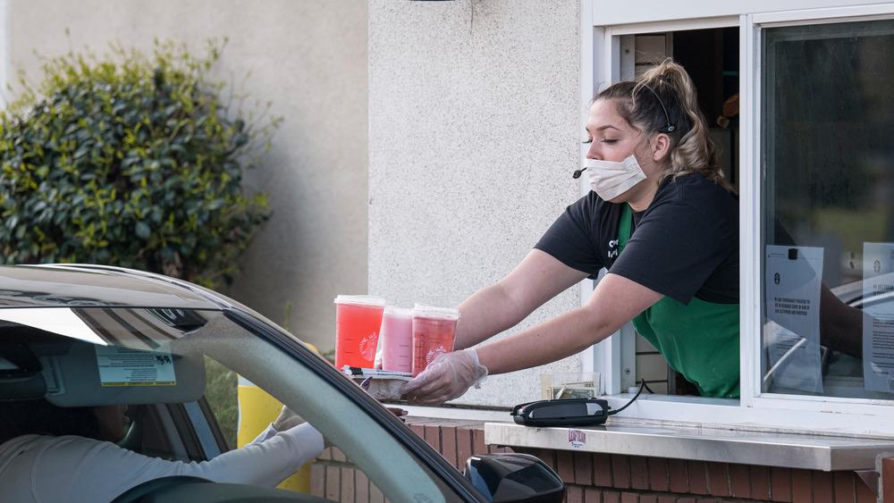 Starbucks employee giving drinks