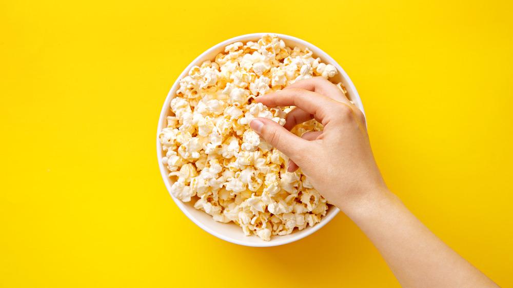 Hand taking popcorn