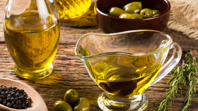 Glass boat of olive oil on table