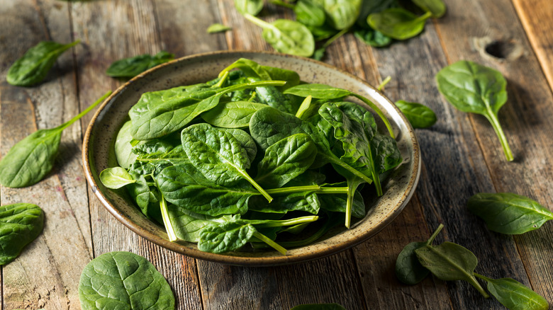 A bowl of spinach on a wooden table, surrounded by loose leaves