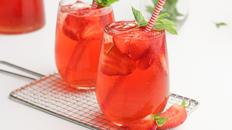 Two glasses of strawberry sweet tea with stripped straws garnished with strawberries and mint