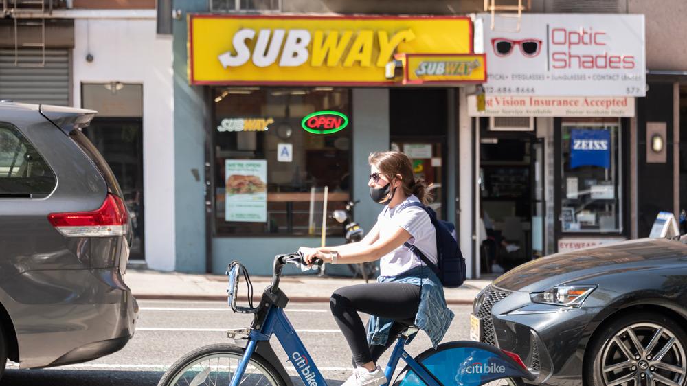 Woman riding a bike outside of Subway