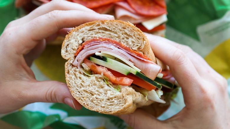 Hands holding a Subway sandwich