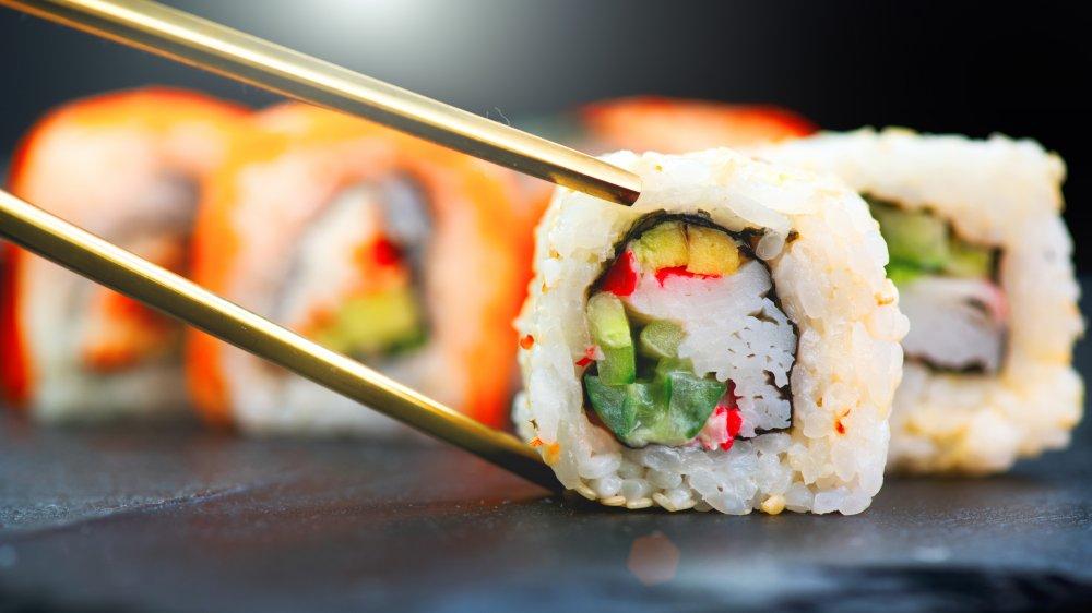 chopsticks picking up a piece of sushi