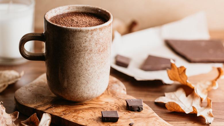 Mug of hot chocolate alongside fallen leaves
