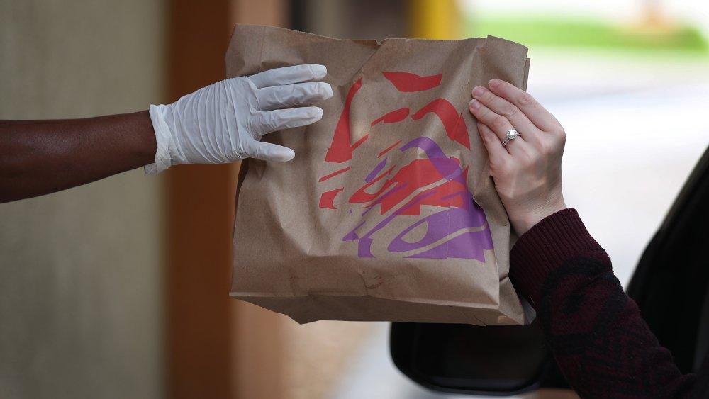 Person receiving Taco Bell order through drive through