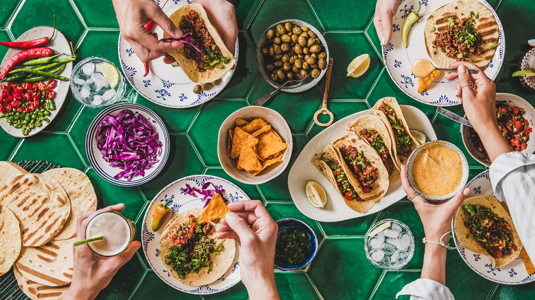 Hands preparing tacos on a green tile background