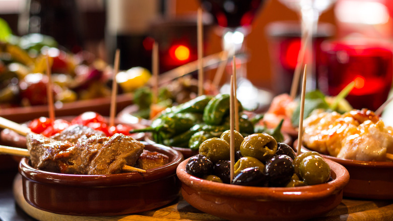 Small ceramic dishes of olives and other tapas with toothpicks