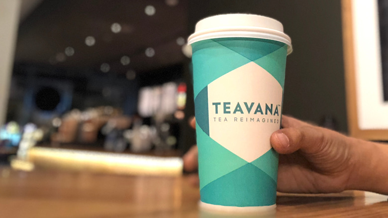 Person holding paper cup with the word Teavana