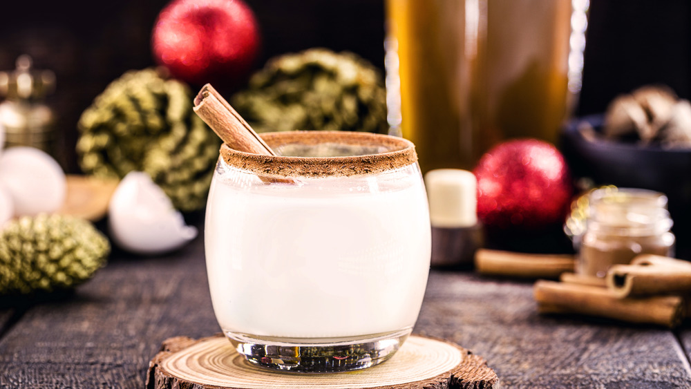glass of eggnog with Christmas decorations in background
