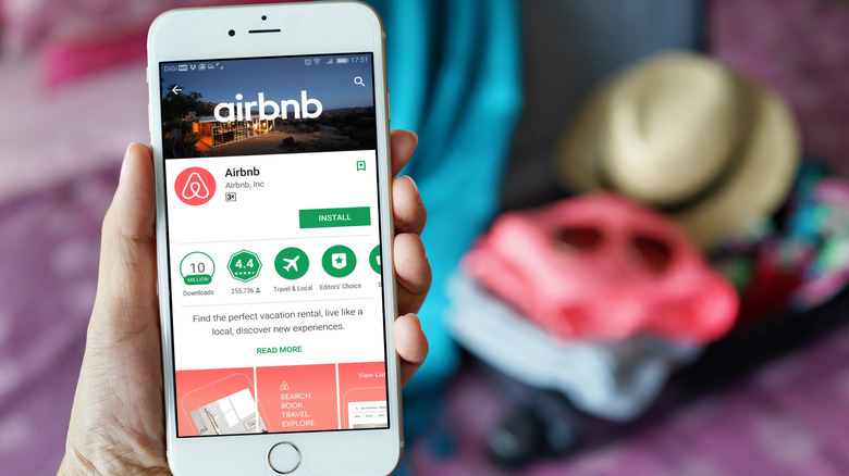 Person holding phone showing Airbnb app