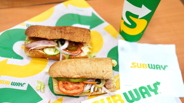 Subway sandwiches on packaging next to cup