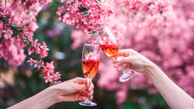 Two hands holding cocktails in front of cherry blossoms
