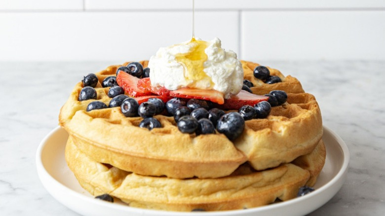 fluffy golden brown belgian waffles topped with fresh berries, whipped cream, and maple syrup