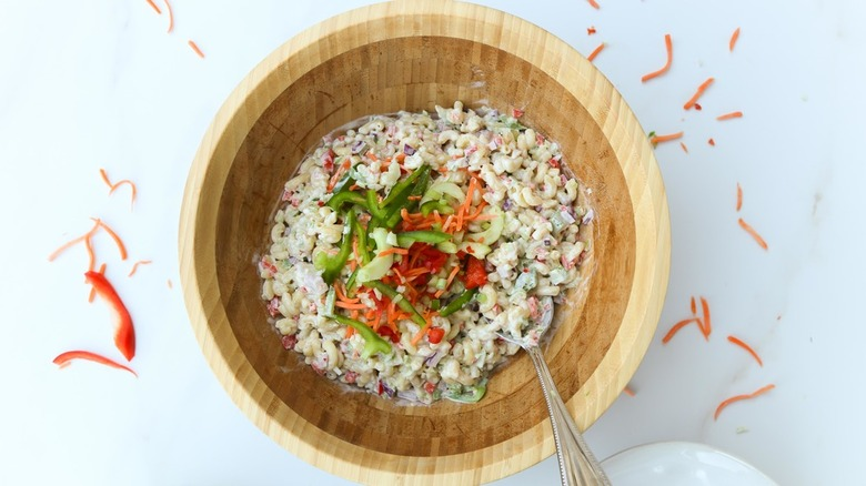 macaroni salad in wooden bowl with colorful veggies on top