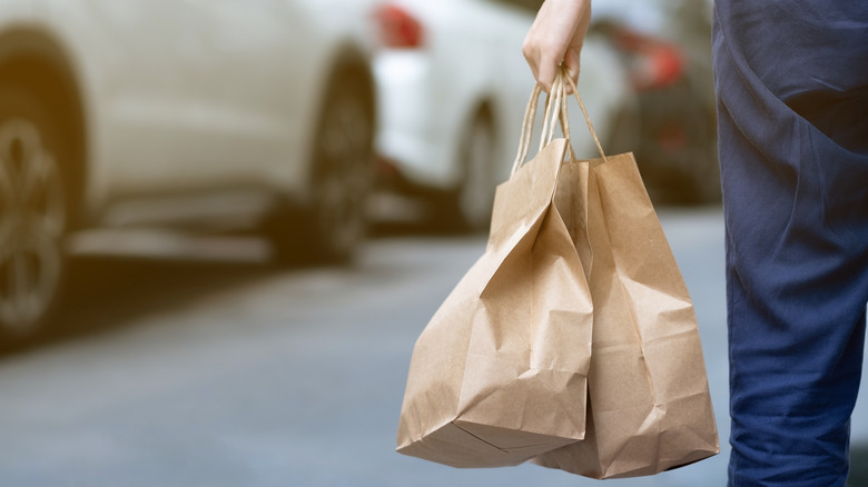 person carrying take-away food in brown bags