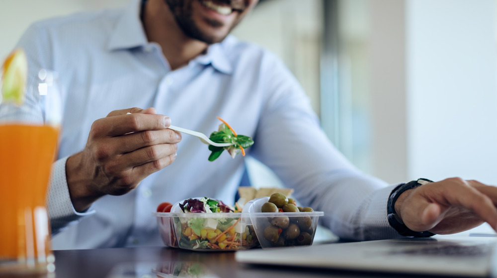 man eating lunch at his desk